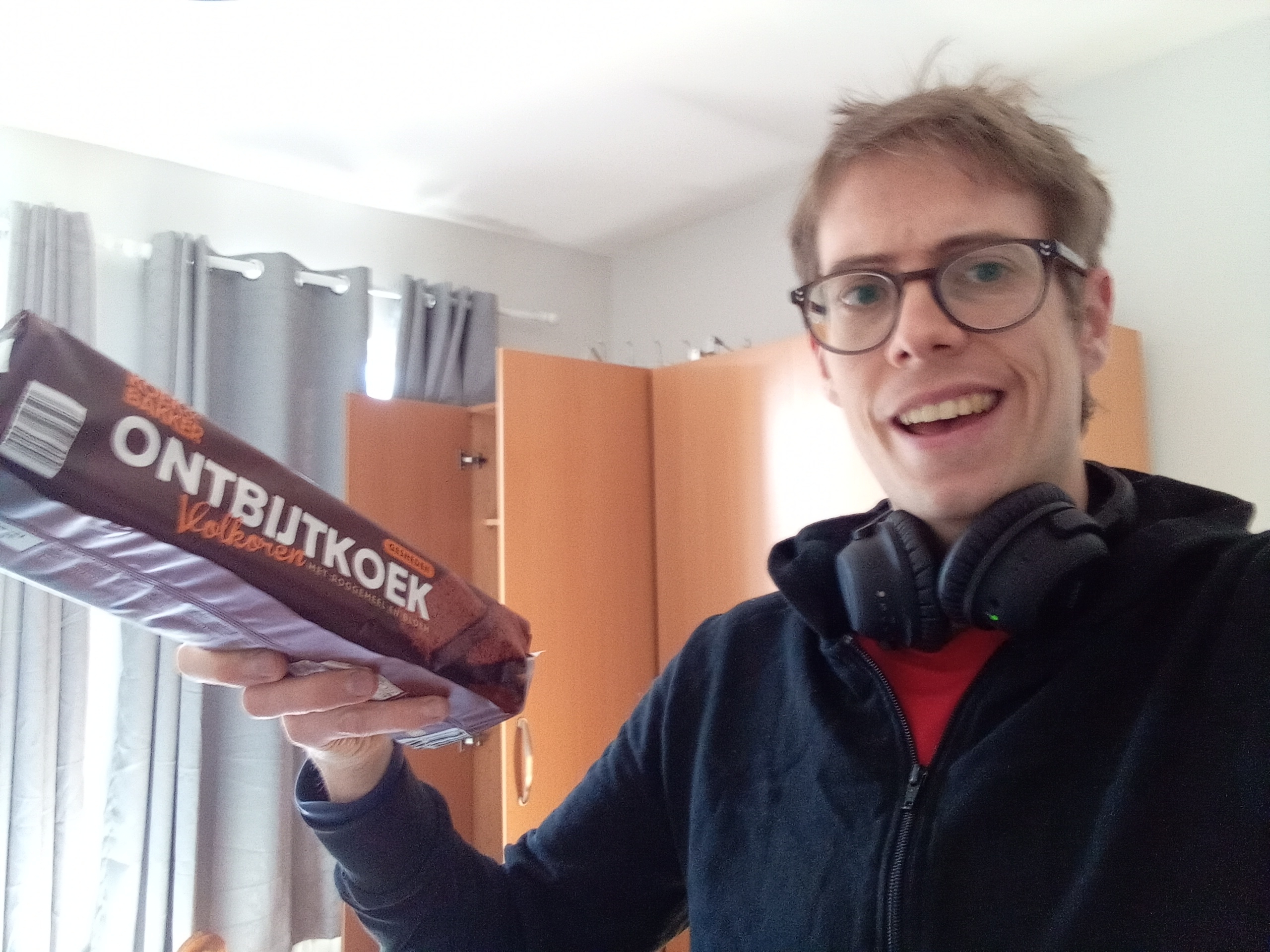 A white man (Jorik) wearing glasses and headphones around his neck. He is also wearing a black hoodie and red t-shirt. He is holding up a packet of Ontbijtkoek and wears a quizzical expression.