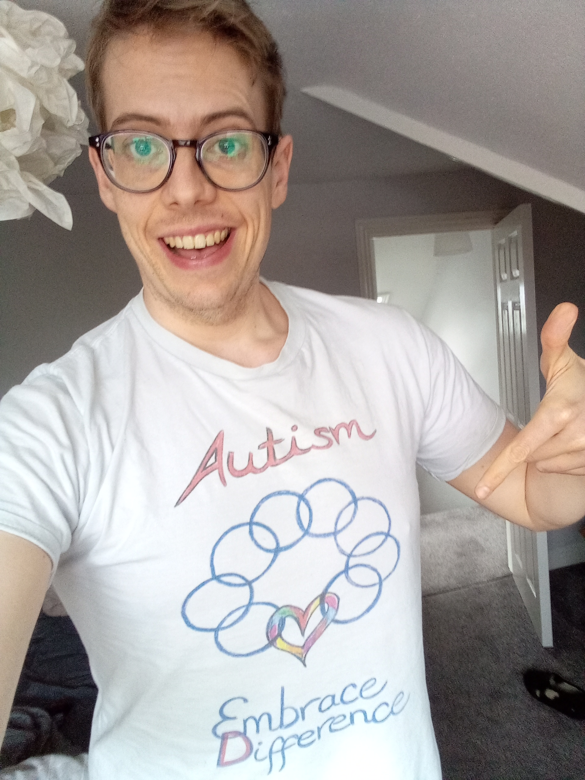 """A 33 year old white autistic with light blonde hair is pointing at his white t-shirt, which says """"Autism"""" and Embrace Diversity"""". Between the two words is an image of a series of interlocking circles, culminating in a heart with rainbow colours."""