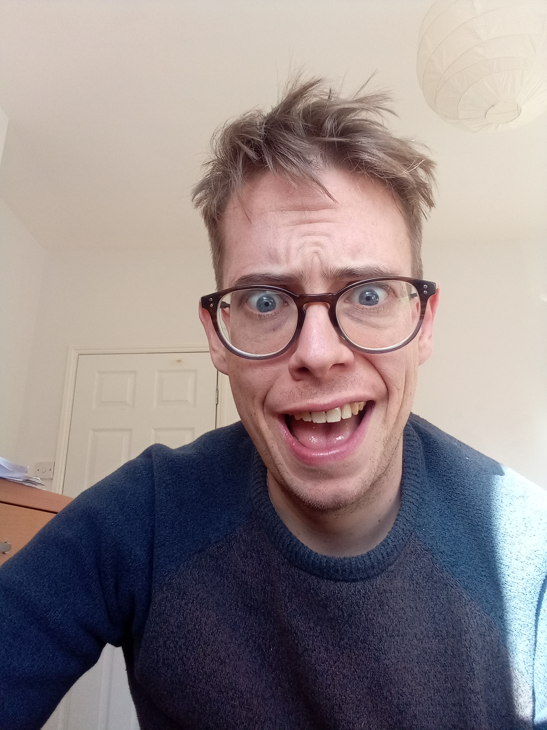An image of Jorik, a white 33-year old autistic gay with soft hair, glasses and an expression of baffled hilarity on his face.